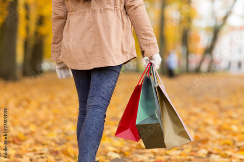 Fotomural  sale, consumerism, season and people concept - woman with shopping bags walking