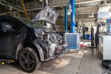 The Black Car In The Body Of The Hatchback Is Preparing For Painting The Body With The Help Of Leveling In The Places Of Damage To Exterior Elements In A Workshop For Repair. Auto Service Industry.