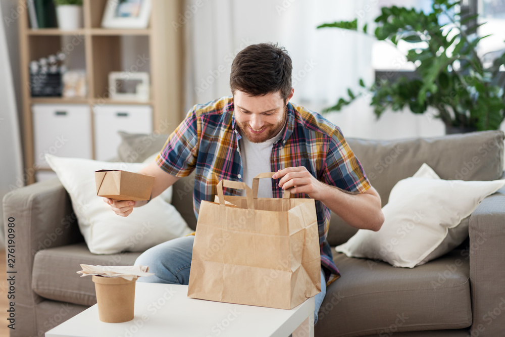 Fototapety, obrazy: consumption, eating and people concept - smiling man unpacking takeaway food at home