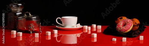 Keuken foto achterwand Cafe Panorama with a Cup of coffee, a donut and sugar on a red glossy table