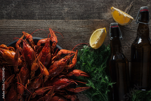 Photo  top view of red lobsters, dill, lemon slices, bottles with beer on wooden surfac