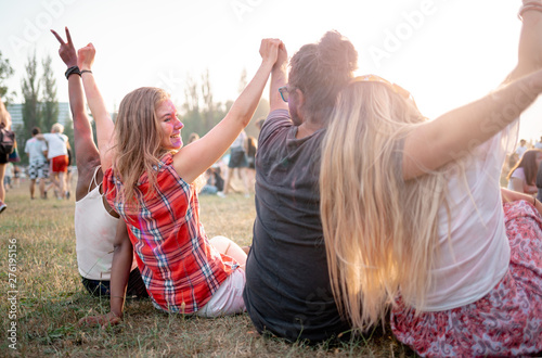 Group of multiethnic people sitting on grass ang having fun at summer music fetival - 276195156