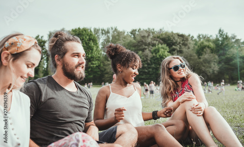 Group of friends sitting on grass and having fun at summer music festival - 276196359