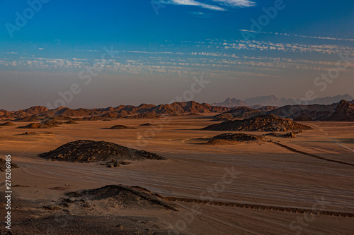 Safari and travel to Africa - extreme adventures or science expedition in a stone desert. Sahara desert at sunrise - mountain landscape with dust on skyline, hills and traces of the off-road car