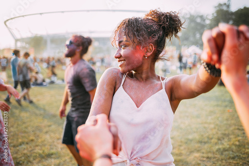 African American young woman with friends dancing at summer holi festival - 276211373