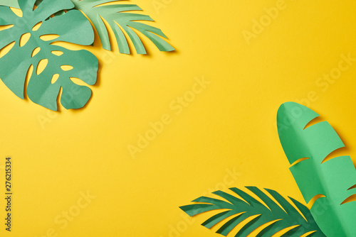 Cuadros en Lienzo top view of paper cut green palm leaves on yellow background with copy space