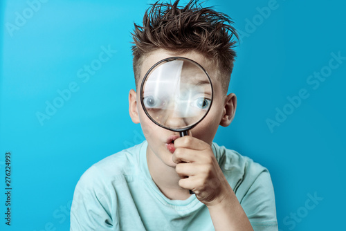 Fotomural  boy in a light t-shirt looking into a large magnifying glass