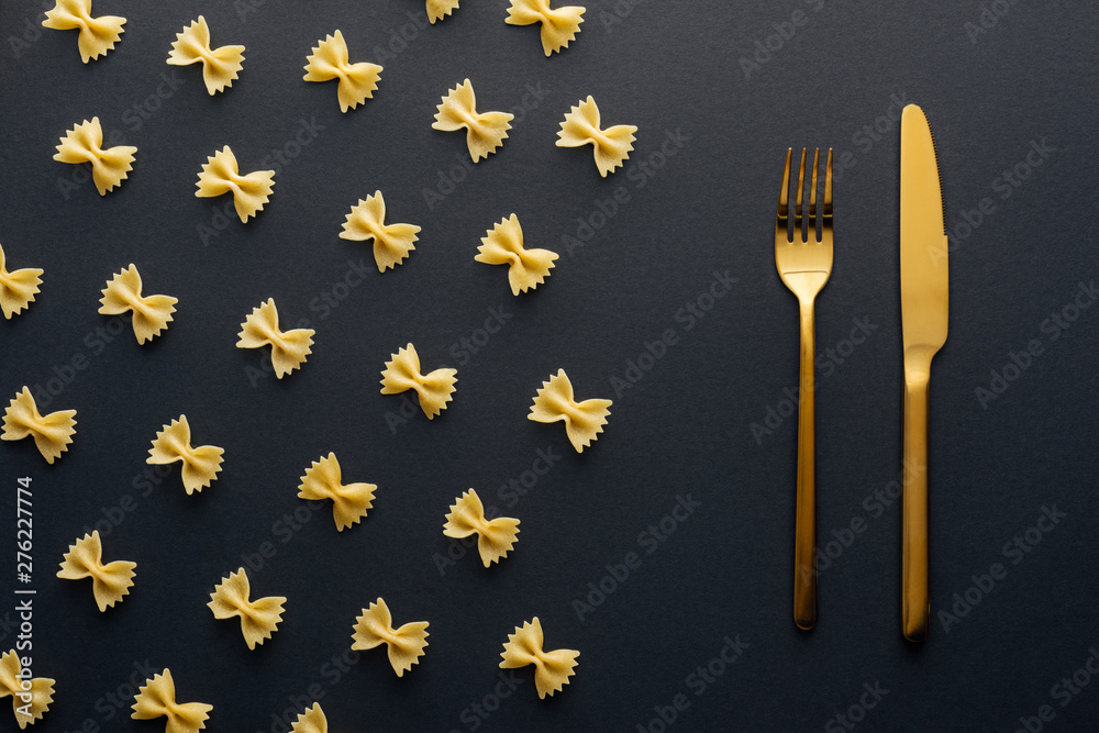 Fototapety, obrazy: flat lay of farfalle pasta near golden knife and fork on black background