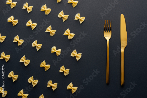 flat lay of farfalle pasta near golden knife and fork on black background