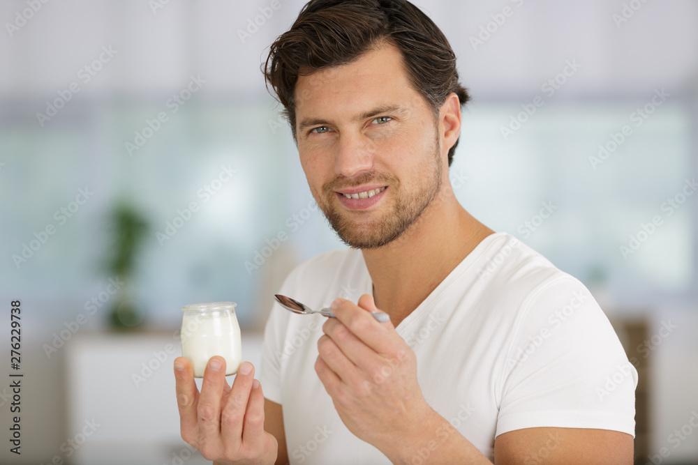 Fototapety, obrazy: man is eating a yogurt
