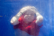 Portrait Of Little Girl Kid Swimming Underwater With Eyes Closed And Scrunched Up Face Holding His Breath