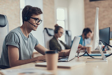 Young Guy In Glasses Is Sitting In The Call Center