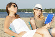 two women relaxing ont he beach one reading a book