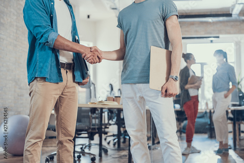 Poster Ouest sauvage Two young male colleagues shaking hands in office