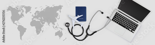 international medical travel insurance concept, stethoscope, passport, laptop computer and airplane on desk office banner with global map