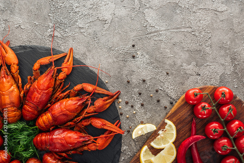 Photo  top view of black plate with red lobsters, green herbs near tomatoes and red pep
