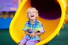 Child On Playground. Kids Play...