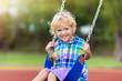 Leinwandbild Motiv Child on playground. swing Kids play outdoor.