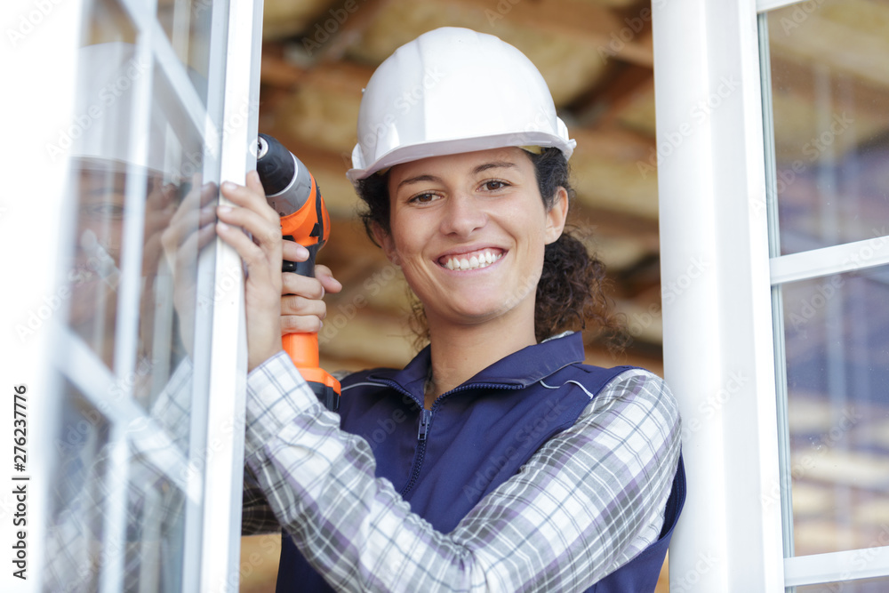 Fototapety, obrazy: woman builder using a drill for fixing a window