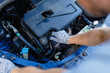 Man's hand unscrews the cap of the oil filler neck of the engine. Mechanic gloves change engine oil, service engine.