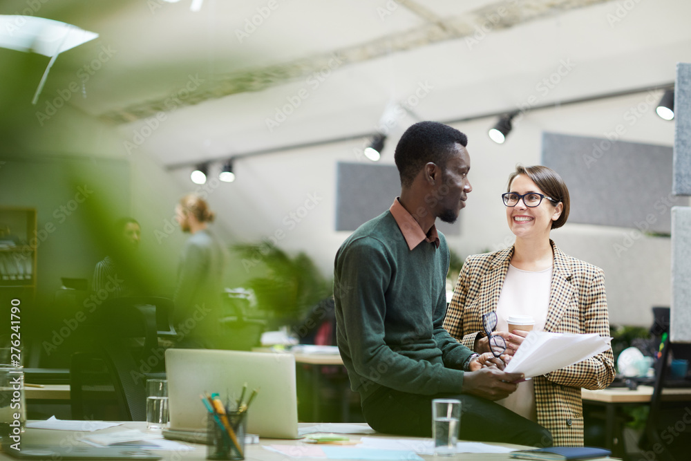 Fototapeta Portrait of young business manager smiling at African-American colleague while chatting at break in office, copy space