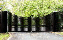 Dark Wooden Driveway Property Entrance Gates Set In Timber Picket Fence With Garden Shrubs And Trees In Background