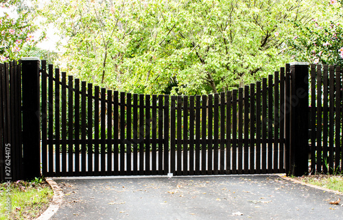 Obraz Dark wooden driveway property entrance gates set in timber picket fence with garden shrubs and trees in background - fototapety do salonu