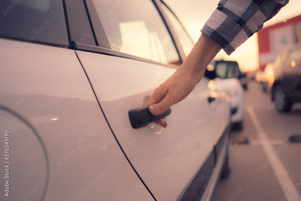 Fototapety, obrazy: casual person opens the white  car door on the parking, car rental concept