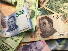 Many Mixed Mexican Peso Bills Spread Over A Wooden Desk