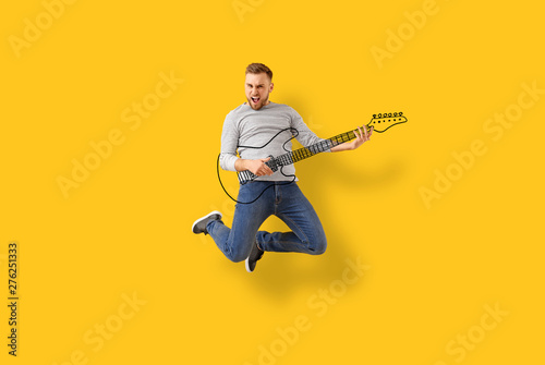 Jumping young man with drawn guitar on color background - 276251333