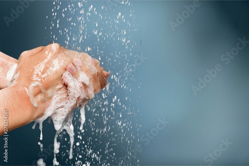 Fotografiet Man washing hands in clean water on blue background