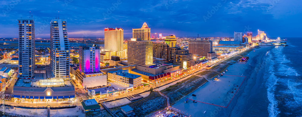 Fototapeta Aerial panorama of Atlantic city along the boardwalk at dusk. In the 1980s, Atlantic City achieved nationwide attention as a gambling resort and currently has nine large casinos.