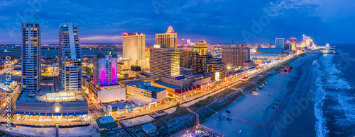 Aerial panorama of Atlantic city along the boardwalk at dusk. In the 1980s, Atlantic City achieved nationwide attention as a gambling resort and currently has nine large casinos. - 276255350