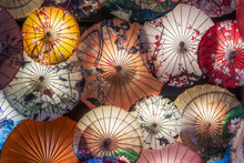 Multi Colored Chinese Umbrellas Hanging On A Wall Illuminated At Night