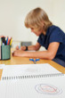 Desk with opened textbook with scribble and schoolboy drawing in background