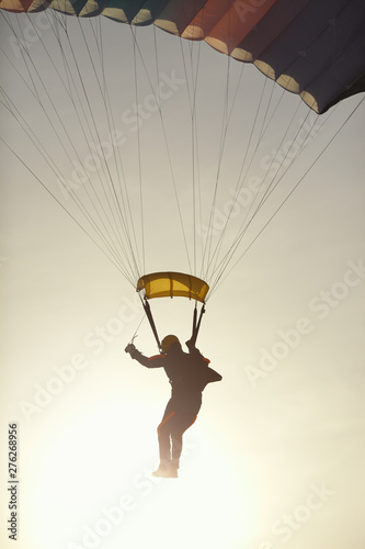 Photo Abstract skydiver silhouette landing with a parachute in a back light, close-up