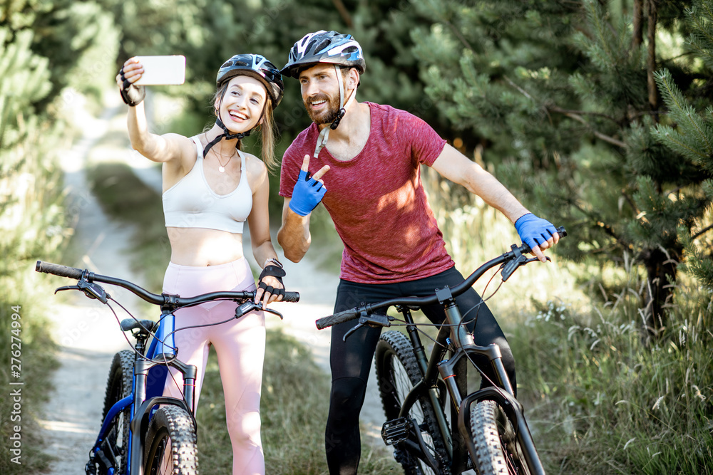 Fototapety, obrazy: Young sports couple taking selfie photo with smartphone while riding mountain bicycles on the forest road during the summer time