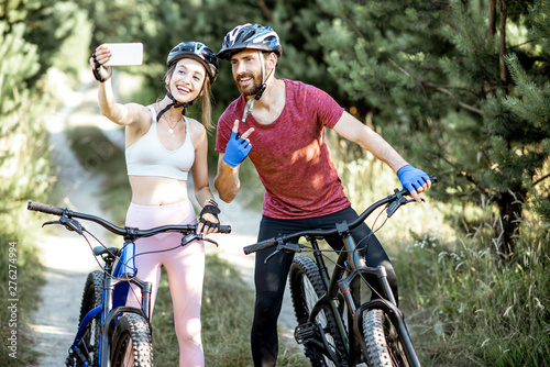 Young sports couple taking selfie photo with smartphone while riding mountain bicycles on the forest road during the summer time