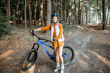 Portrait of a young woman with mountain bicycle in the forest