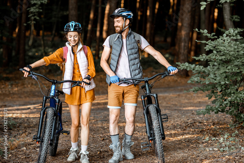 Poster Ecole de Danse Young couple dressed casually standing together with mountain bicycles, traveling in the forest during the summer vacations
