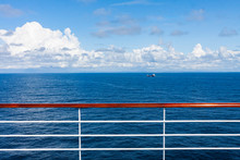 SEA LANDSCAPE FROM THE CRUISE COVER AND WOODEN RAILING IN CLOSE UP