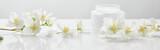 Fototapeta Kwiaty - panoramic shot of jasmine flowers on white surface near jar with cream