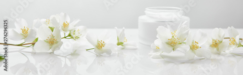Fotobehang Bloemenwinkel panoramic shot of jasmine flowers on white surface near jar with cream