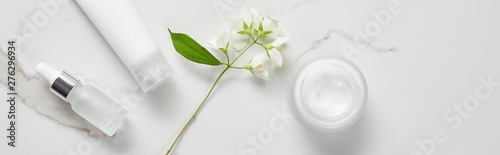 panoramic shot of jasmine, cosmetic glass bottle, jar with cream and moisturizer tube on white surface