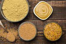 Mustard. Different Types Of Mustard, Dry Mustard Grains Sauce And Mustard Powder In A Bowl On A Brown Wooden Table. Close-up. View From Above