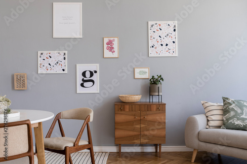Fotografía  Design scandinavian home interior of open space with stylish chairs, family table wooden commode, gray sofa, accessories and mock up posters gallery wall