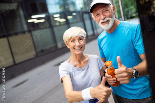 plakat Happy senior couple staying fit by sport running