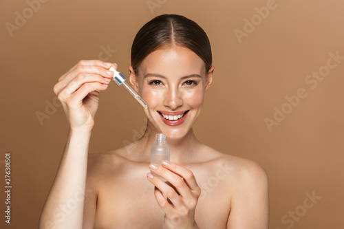 Poster Spa Beautiful happy young amazing woman posing isolated over brown chocolate background wall holding oil drop serum.