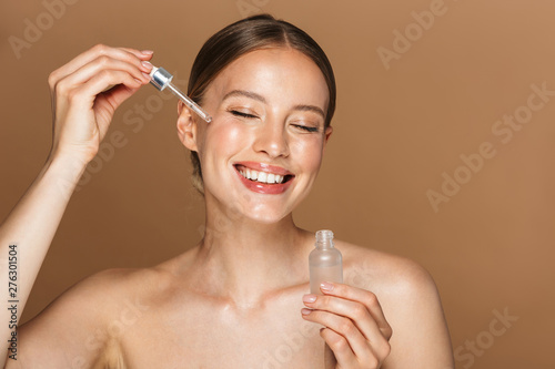 Fotografia Beautiful happy young amazing woman posing isolated over brown chocolate background wall holding oil drop serum
