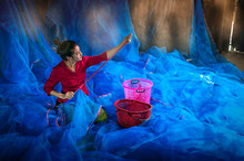 Traditional And Culture Of Asian Woman Repairing Blue Fishing Nets In Fishing Village  , South Thailand, Asia.